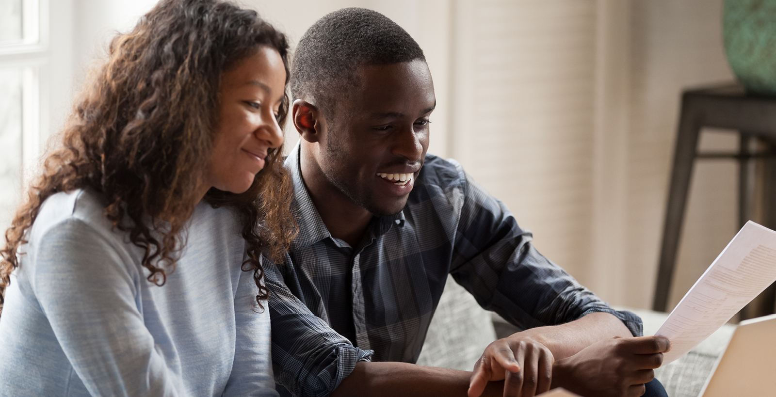 A young couple smiles while reading paperwork