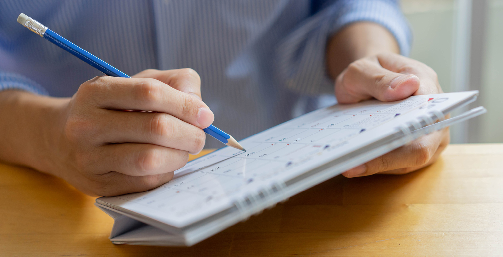 A man holds a desktop calendar in his hands, and is writing on it with a blue pencil