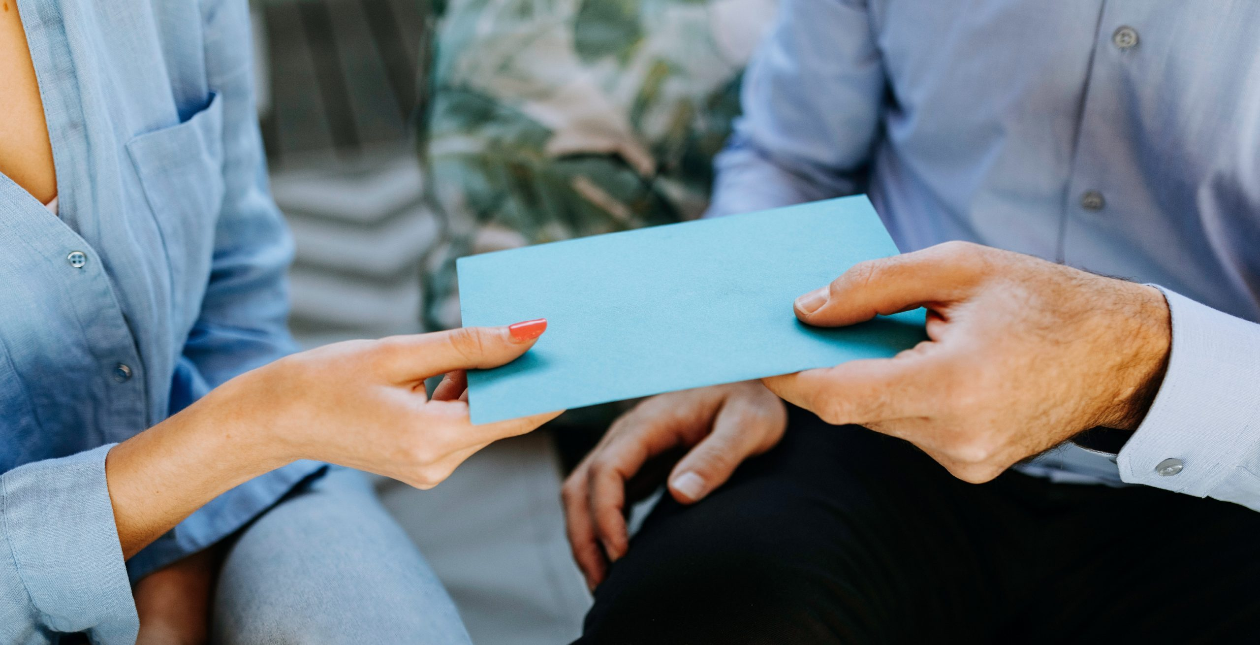 An close-up image of an older person and a younger person handing off a blue envelope.