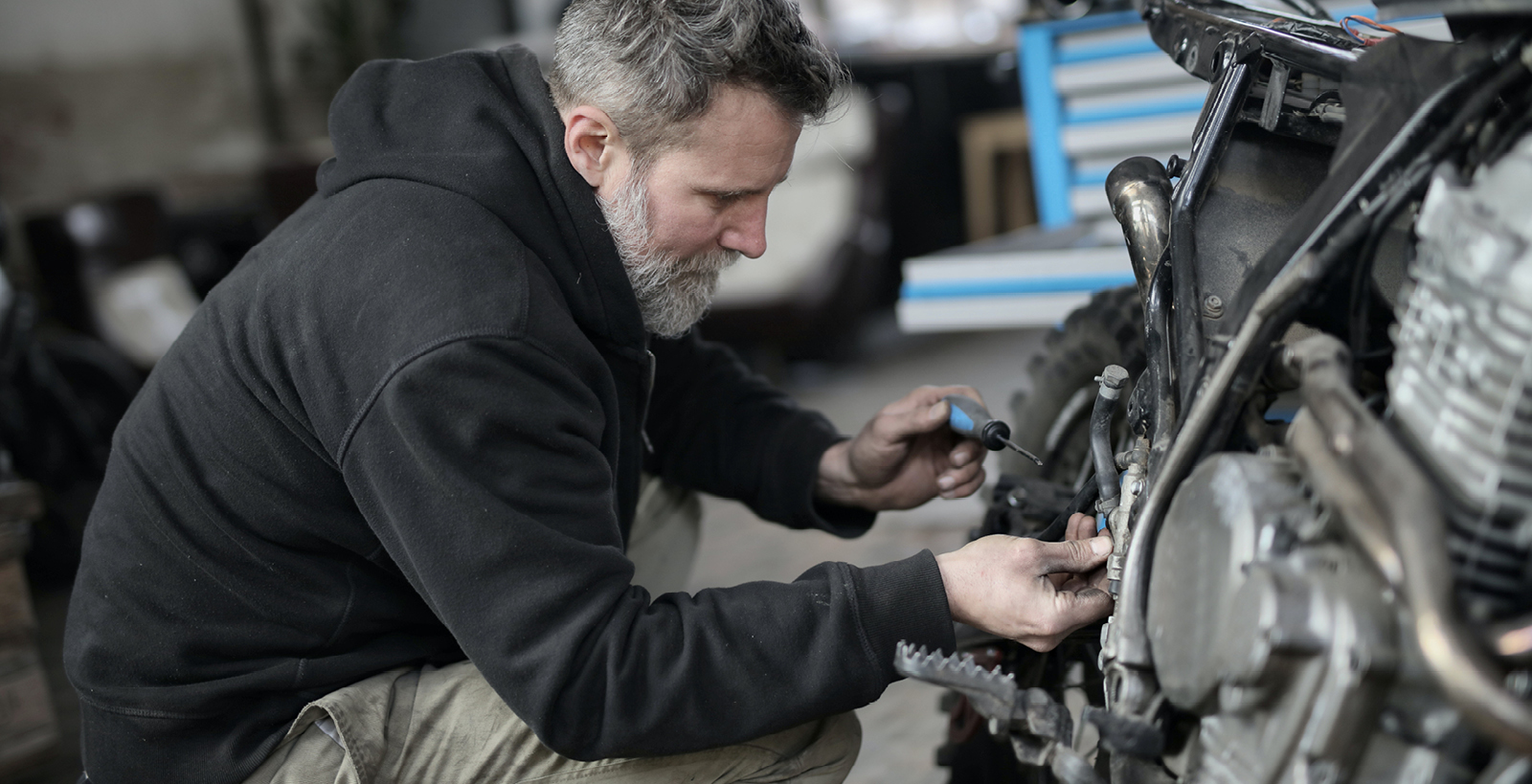 A man with a gray beard kneels to make repairs on a motorcycle