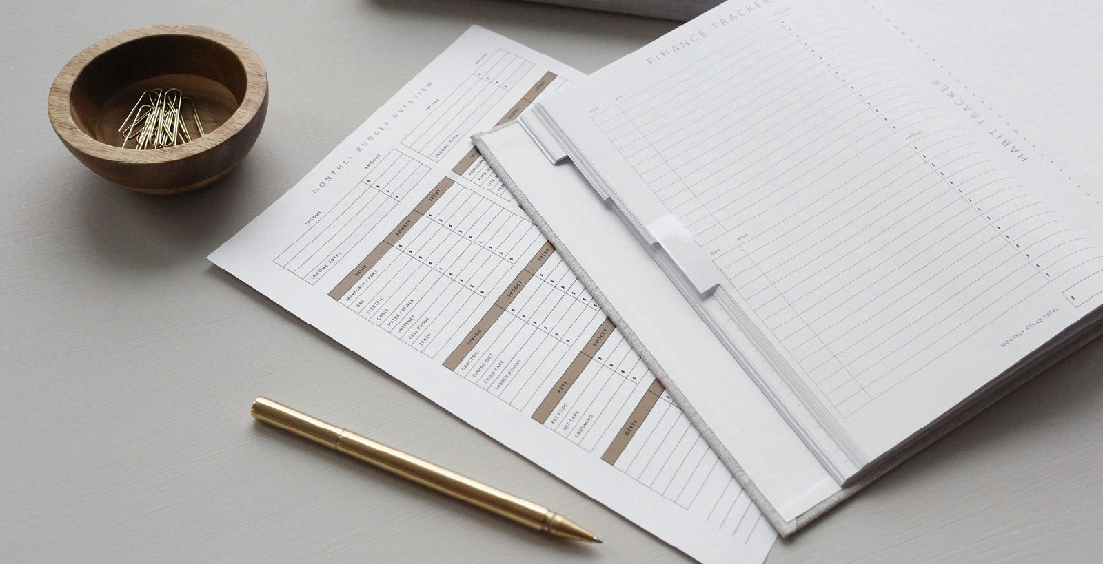 A budget sheet and financial tracking planner lay open on a gray desk beside a rose-gold pen and small wooden bowl of paperclips.